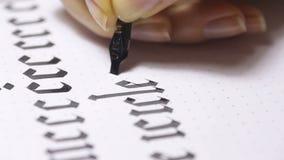 A mulher escreve a pena com letras caligráficas video estoque
