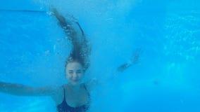 Mulher escultural alegre no roupa de banho com salto inflável do anel na associação no recurso caro durante férias de verão filme