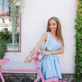 Mulher escultural inspirada que está no fundo com a bicicleta cor-de-rosa no vestido azul Estilo de vida do conceito foto de stock royalty free