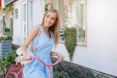 Mulher escultural inspirada que está no fundo com a bicicleta cor-de-rosa no vestido azul Estilo de vida do conceito imagens de stock royalty free