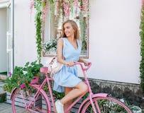 Mulher escultural inspirada que está no fundo com a bicicleta cor-de-rosa no vestido azul Estilo de vida do conceito fotos de stock