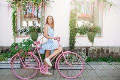 Mulher escultural inspirada que está no fundo com a bicicleta cor-de-rosa no vestido azul Estilo de vida do conceito fotos de stock royalty free