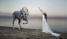 Mulher escultural que está oposto ao cavalo Imagens de Stock Royalty Free