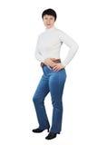 Mulher escultural vestida no Turtleneck e na calças de ganga feitos malha branco foto de stock royalty free