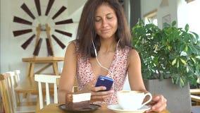 A mulher escuta a música no smartphone com fones de ouvido filme