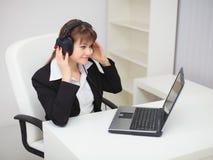 A mulher escuta a música por meio do portátil Imagem de Stock Royalty Free