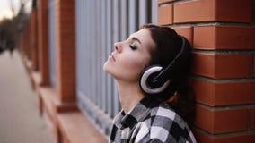 A mulher escuta pensativamente a música nos fones de ouvido, inclinando-se na parede da cerca na rua Meus olhos são vídeos de arquivo