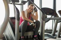 Mulher esgotada no gym que limpa fora do suor foto de stock