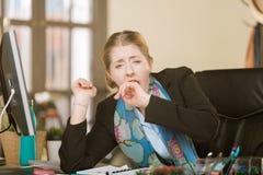Mulher esgotada ou furada que boceja em sua mesa imagens de stock