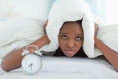 Mulher esgotada que cobre suas orelhas com um duvet Fotos de Stock Royalty Free