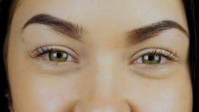 A mulher espalha suas palmas na frente de sua cara e demonstra seus olhos com lentes de contato vídeos de arquivo