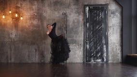 A mulher espanhola apaixonado está dançando o tango apenas em uma sala dramática