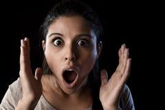 A mulher espanhola assustado bonita nova em choque e a surpresa enfrentam a expressão isoladas no preto imagens de stock