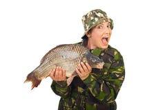 Mulher espantada do fisher que prende a carpa grande Imagem de Stock Royalty Free