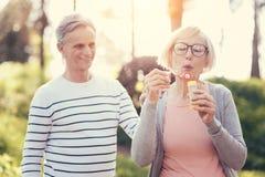 Mulher esperta deleitada que guarda uma garrafa das bolhas de sabão Fotos de Stock Royalty Free