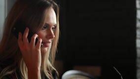 Mulher esperta do close-up que usa o telefone e o portátil espertos, estilo de vida social dos meios da nova geração para viver,  vídeos de arquivo