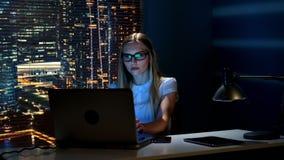 Mulher esperta nos monóculos que lê a mensagem no smartphone ao trabalhar no computador filme