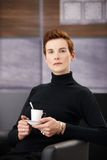 Mulher esperta que come o café na poltrona Fotografia de Stock