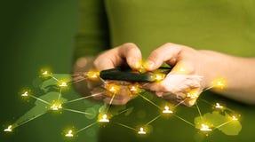 Mulher esperta que guarda o telefone com o connecti social da rede dos meios foto de stock royalty free