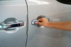 A mulher está abrindo a porta de carro imagem de stock