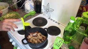A mulher está agitando partes fritadas de galinha e cenouras fritadas Adicione o sal do abanador de sal filme