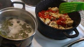 A mulher está agitando partes fritadas de galinha e cenouras fritadas Em seguida em uma caçarola estão os espaguetes preparados vídeos de arquivo