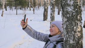 A mulher está andando nas madeiras O viajante é fotografado no telefone na menina da floresta faz o selfie e comunica-se com filme