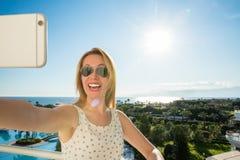 A mulher está apontando com seu dedo ao mar de um balkony nas férias de verão fotos de stock royalty free
