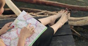 A mulher está apontando uma rota ao destino que senta-se no cais do rio, close up do mapa video estoque