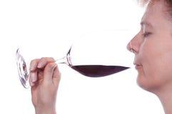 A mulher está apreciando um vidro do vinho vermelho Fotografia de Stock