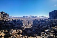 A mulher est? apreciando a vista das ru?nas da fortaleza Borgarvirki de viquingue em Isl?ndia foto de stock