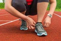 A mulher está atando suas sapatas em uma pista de atletismo do estádio Imagens de Stock Royalty Free