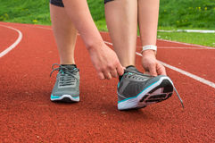 A mulher está atando suas sapatas em uma pista de atletismo do estádio Imagens de Stock