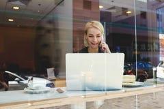 A mulher está chamando com telefone celular durante a conversação video através do laptop portátil Fotos de Stock Royalty Free