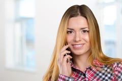 A mulher está chamando com um telefone móvel Imagens de Stock