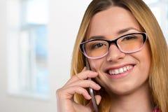 A mulher está chamando com um telefone móvel Foto de Stock