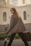 A mulher está com a mala de viagem na frente do hotel Foto de Stock Royalty Free