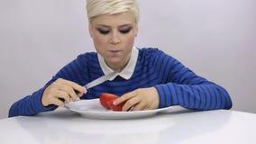 A mulher está comendo o tomate vídeos de arquivo