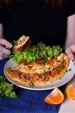 A mulher está comendo uma parte de omeleta com uma forquilha imagem de stock royalty free