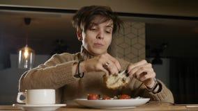 A mulher está comendo vegetais no café video estoque