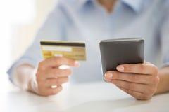 A mulher está comprando no Internet com o cartão do telefone celular e de crédito Foto de Stock