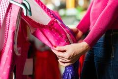 A mulher está comprando Tracht ou dirndl em uma loja Fotos de Stock Royalty Free