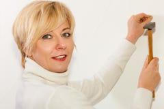 A mulher está conduzindo um prego em uma parede fotos de stock