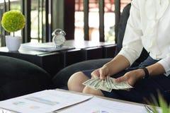 A mulher está contando o dinheiro, mulher de negócios que trabalha o conselheiro financeiro fotos de stock
