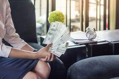 A mulher está contando o dinheiro, mulher de negócios que trabalha o conselheiro financeiro foto de stock