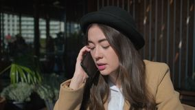 A mulher está conversando pelo telefone celular no café na primavera, câmera está aproximando-se vídeos de arquivo