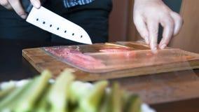 A mulher está cortando peixes vermelhos, truta que a faixa empacotou no bloco de vácuo plástico em uma placa de madeira As mãos g fotos de stock royalty free