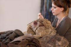 A mulher está costurando uma máscara e um traje do espantalho imagem de stock