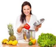 A mulher está cozinhando alimentos frescos Imagem de Stock