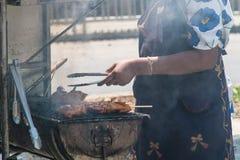 A mulher está cozinhando brochettes da galinha no assado na rua fotografia de stock